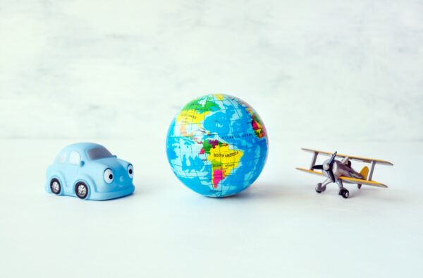 Travel, adventure, vacation concept. Toy yellow air plane, blue car and globe earth ball, map on
